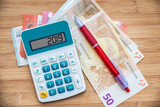 2019 written on a calculator and euros banknotes on wooden background - 229149918
