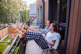 Start of the day. Joyful happy couple sitting on the balcony while enjoying their morning - 229153595