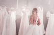 Difficult choice. Beautiful blonde woman standing in front of wedding dresses while thinking about what to choose