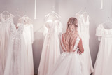 Difficult choice. Beautiful blonde woman standing in front of wedding dresses while thinking about what to choose - 229160592