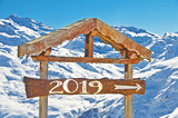 2019 written on a wooden direction sign, snow mountain landscape on the background - 229162540