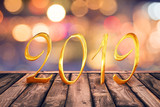 2019, golden numbers on wood table with blurred lights gold bokeh abstract background - 229162787