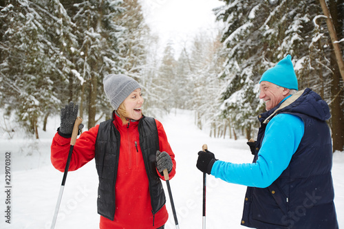 Two skiers greeting each other during training while passing by in winter forest - 229170302