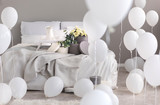 Balloons in industrial stylish bedroom with grey bedding, trey with coffee cups and round boxes with flowers on th bed - 229182128