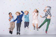 Happy multicultural group of kids jumping against colorful wallpaper