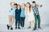 Multicultural group of children against colorful wallpaper. Young friends in the school - 229182376