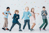 Smiling girls and boys dancing together in the school against colorful wallpaper