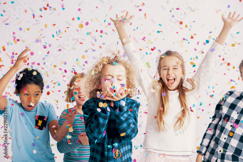 Foto Murales Happy multicultural group of kids having fun during birthday party with confetti