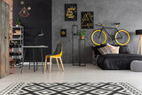 Chair at desk and patterned carpet in grey teenager's room interior with posters and bike. Real photo - 229182929