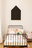 Blackboard above a metal bed with funny pillows in a teenager room interior. Real photo - 229182971