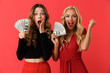 Emotional excited young friends women standing isolated over red background holding money.