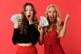 Emotional excited young friends women standing isolated over red background holding money. - 229184705