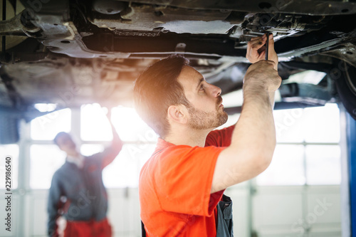 Wall mural Car mechanics working at automotive service center