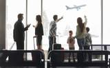 Gruppe Reisende am Flughafen Terminal vor Flugzeug - 229189915