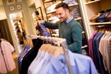 Portrait of a young man looking at clothes to buy at shop - 229200367