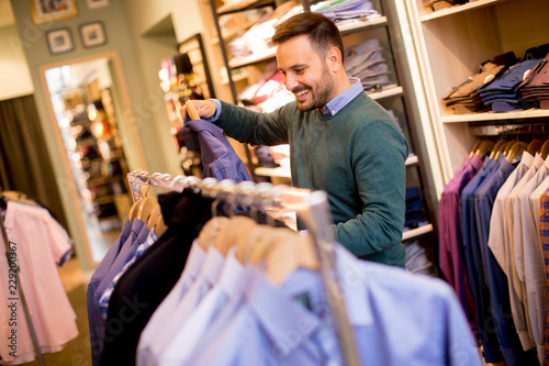 Foto Murales Portrait of a young man looking at clothes to buy at shop