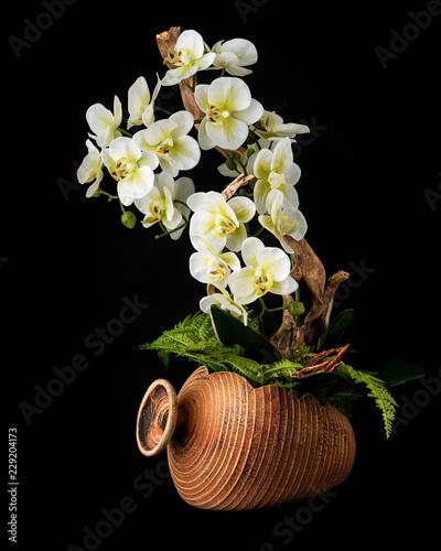 Kwiatowy układ z sztuczne kwiaty orchidei w stary ceramiczny doniczka.