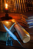 Quill pen and a rolled papyrus sheet on a wooden table with old books - 229216376