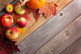 Rustic Autumn Wooden Background Framed by Apples and Fall Maple Leaves