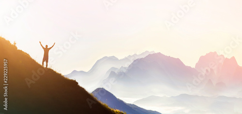 Leinwandbild Motiv Man on peak of mountain. Emotional scene. Young man with backpack standing with raised hands on top of a mountain and enjoying mountain view. Hiker on the mountain top. Sport and active life concept.