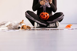 young woman makes Halloween garland.Creative DIY . Home decor project party.Halloween crafts inspiration. Cuet small dog besides - 229229555