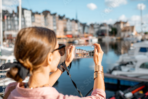 Poster Young woman tourist enjoying beautiful view on the harbour traveling in Honfleur town in Normandy, France