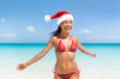 Christmas Caribbean beach tropical getaway Santa Claus woman. Happy Asian bikini girl with slim body for weight loss new year resolution concept. Travel vacation holidays under the tropical sun.