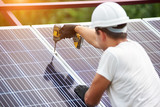 Back view of young technician in helmet connecting solar photo voltaic panel to metal platform using electrical screwdriver on shiny surface background. Stand-alone solar panel system installation. - 229245326