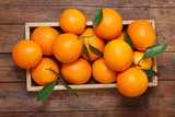 fresh orange fruits in a box on wooden table, top view - 229250538