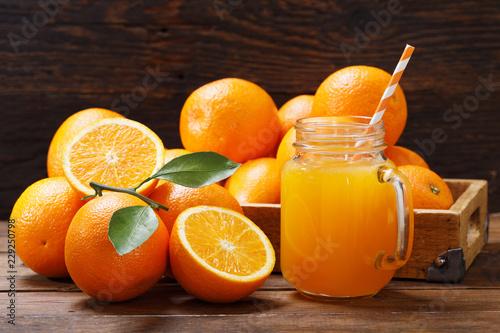 Foto Murales glass jar of fresh orange juice with fresh fruits