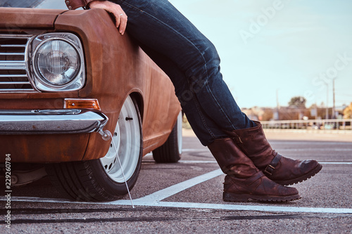 Leinwandbild Motiv Cropped photo of male in jeans and boots leaning on retro car in the city parking.