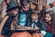 Man and Children in Costumes Reading Book Together