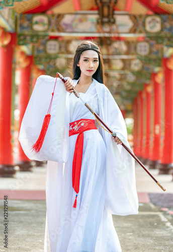 Beautiful Chinese woman with a traditional suit with a sharp sword in her hands, Beautiful and belligerent face, Young woman with a samurai bushido katana sword © analysis121980