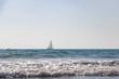 Sailboat on horizon of an empty blue ocean