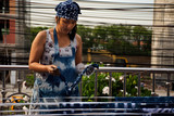Thai women working Indigenous knowledge of thailand tie batik dyeing indigo color and hanging process dry fabric in the sun at outdoor - 229297576