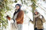 Waist up portrait of happy young couple  skiing in winter forest and looking at camera, focus on woman in front