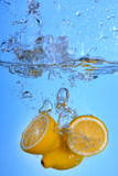 Tropical fruits fall deeply under water with a big splash lemon drop into water splashing on blue backgfround