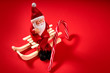 christmas santa claus figurine sitting on a sled on a red background