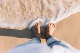 crop barefoot man relaxing on the beach