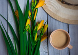 a bouquet of yellow lilies, a hat and a Cup of coffee on a wooden table, breakfast