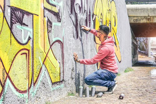 Street graffiti artist painting with a color spray can a dark monster skull graffiti on the wall in the city outdoor - Urban, lifestyle contemporary street art concept - Main focus on his hand - 229349376
