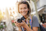 Attractive young woman taking photographs on SLR - 229351532