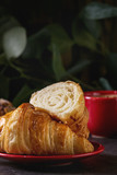 Fresh baked whole and sliced croissant with red cup of coffee espresso on black table with eucalyptus branch. Dark rustic style. Close up