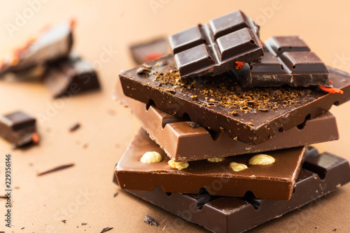 Chocolate bars with nuts, goji berries and coffee beans on a brown background