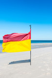 Red-yellow flag on the beach and view of the calm sea from the beach, open space, horizon. - 229369771