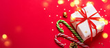 Christmas gift box and candy cane with shining lights. Long banner format - 229375351