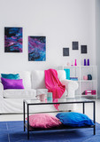 Vertical view of stylish living room with comfortable white couch with pink blanket and blue and purple pillows, cosmos graphics on the wall, real photo