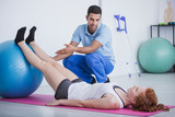 Professional physiotherapist and sportswoman on mat exercising with ball