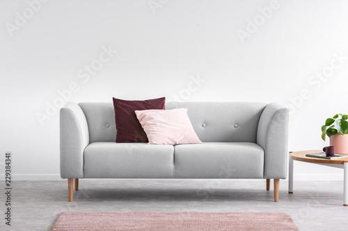 Fioletowa i pastelowa różowa poduszka na szarym wygodnym kanapy w jasnym salonie z różowym dywanem i stolikiem do kawy, prawdziwe zdjęcie z miejsca na kopię na pustej białej ścianie
