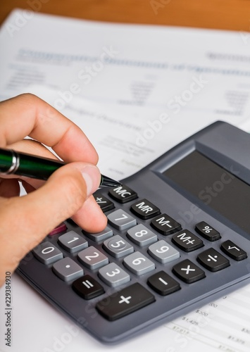 Close-up of a Businessman Using Calculator with Financial - 229384930
